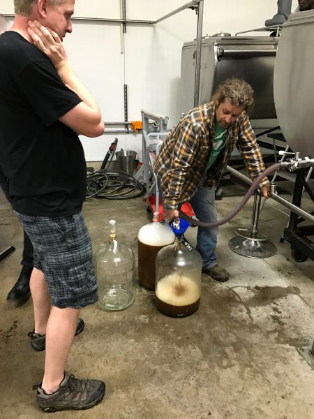 Ian, owner of Frank E's, filling some carboys as Wade looks on.